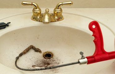 Plumbing snake with clog in a bathroom sink
