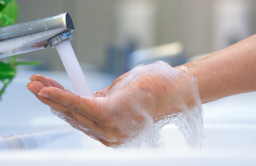 Woman washing hands and deciding between tank vs tankless water heater