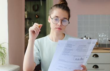 Woman sits at table and finds ways to lower electric bill