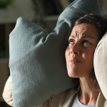 Homeowner plugs ears with pillows to avoid hearing bad furnace noises.
