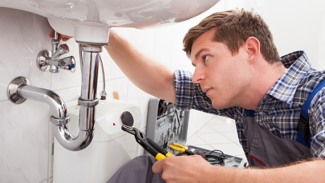Homeowner adjusts sink trap in his bathroom using tips from our plumbing 101 guide