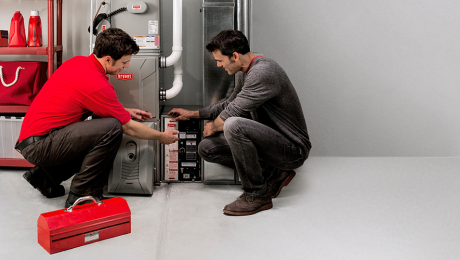 Technician shows male homeowner how to change your air filter near the furnace.
