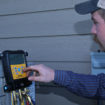 Martens technician in hat and blue shirt performs annual AC maintenance on outdoor unit