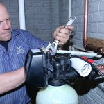 Plumber works on pipes and shares reasons to have your water tested.