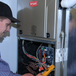 Technician in blue shirt crosses items off his fall furnace checklist.